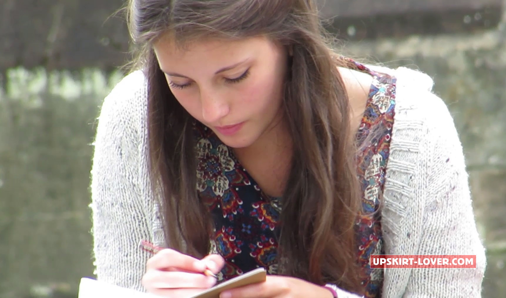 Beautiful young schoolgirl does her homework outside